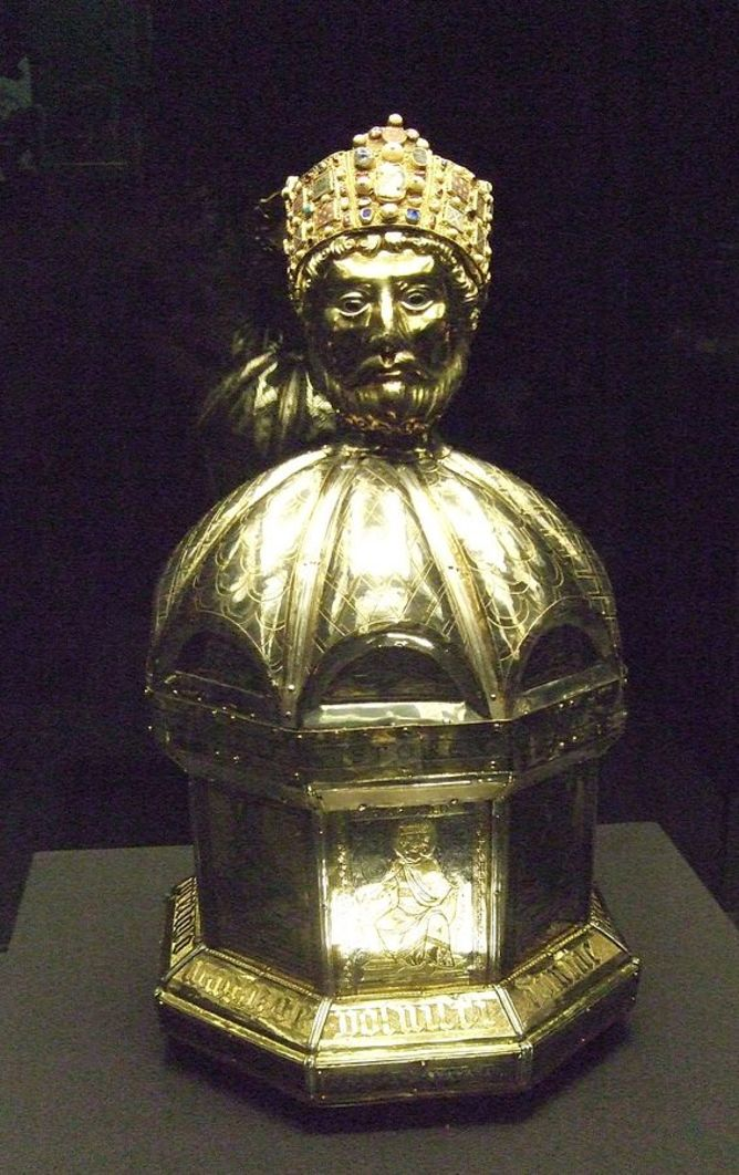 A golden relic of St Oswald stands in the middle of a small table. He wears a jewelled crown with curly hair shown underneath it and is looking at the camera with a serious expression. The base of the relic is ornately carved.