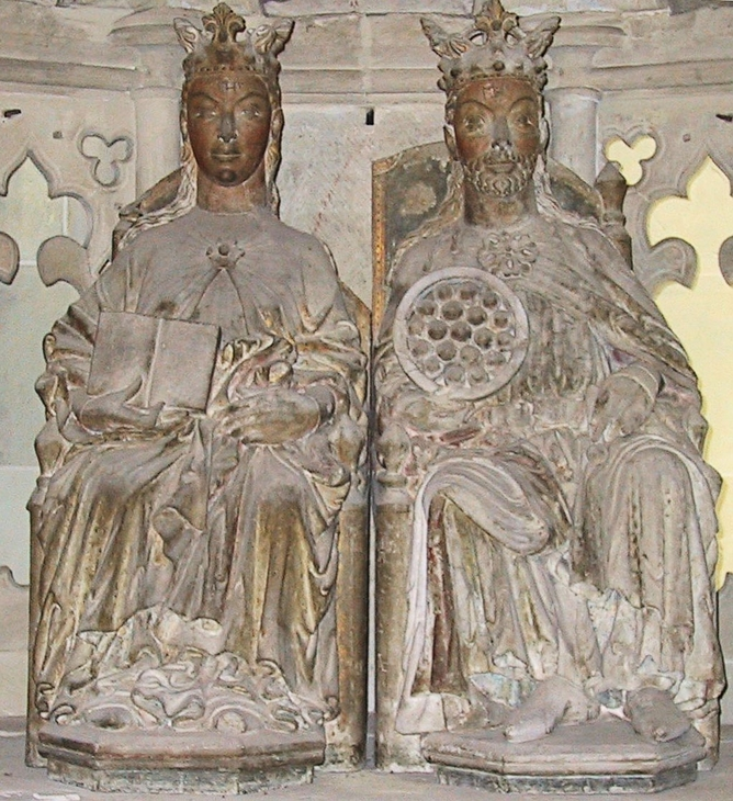 Carved sculptures of Eadgyth and her husband Otto I are sat side by side with each wearing a crown. Their faces are coloured bronze or brown and they wear grey and gold tinted clothing, which is held together in the centre by a brooch detail. She is sat on the left holding a book in one hand and he is sat on the right holding up a medallion.