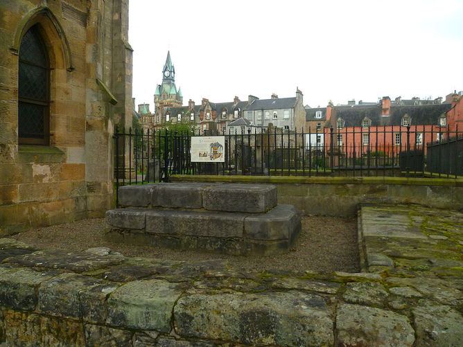 Photograph of the Shrine of St Margaret in Dunfermline which is several large grey stones arrange in two stacked rectangles. The image is taken within the church grounds and shows the local houses and a clocktower in the background behind some black railings.