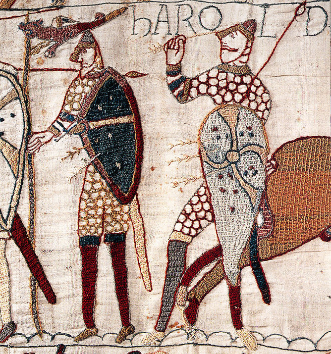 Close-up detail from the Bayeux Tapestry depicting the death of Harold. Harold appears to be pulling an arrow in yellow thread from his eye and is holding a shield stitched with cream thread and red, gold and blue details on it. His chain mail is shown in red thread and depicted as red hoops.