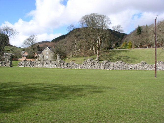 Photograph of Cwmhir Abbey in Wales. There is a landscaped lawn of green going from the bottom of the image to the centre and a rocky wall across the middle separating the landscape. Behind the wall are some houses, one of them beige bricked and one of them red brick. There are hills and greenery behind the houses.