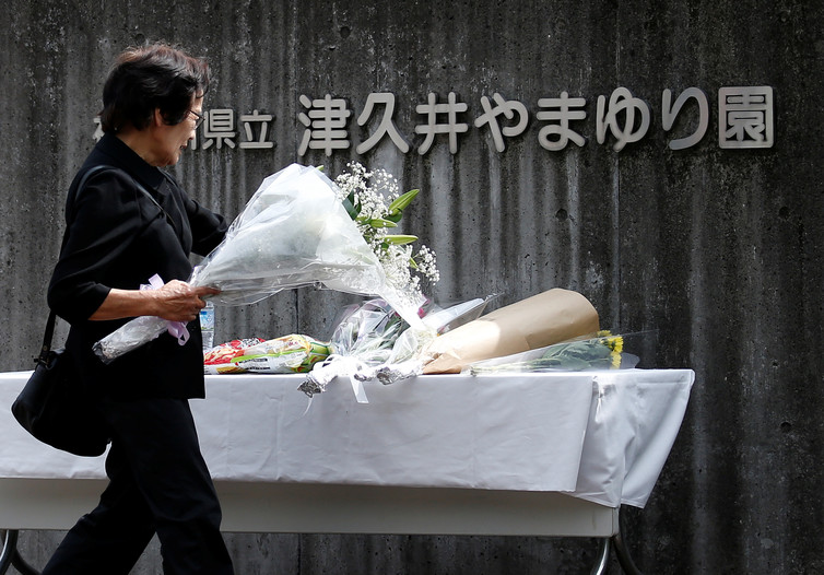 A woman offers flowers to mourn the victims at Sagamihara. Issei Kato