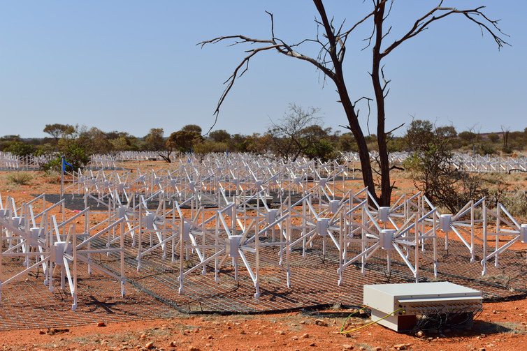 View of about 1% of the Murchison Widefield Array, showing the tiled dipoles used to receive astronomical signals, and a 'beam former', aggregating the signals and controlling the pointing of the instrument. MWA Collaboration