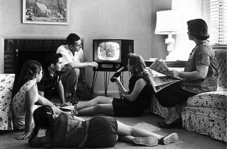 A family huddles around the television in the late 1950s.  National Archives and Records Administration