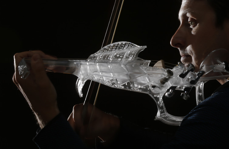 French engineer and professional violinist Laurent Bernadac plays a 3D printed violin made of transparent resin. Credit Christian Hartmann/Reuters