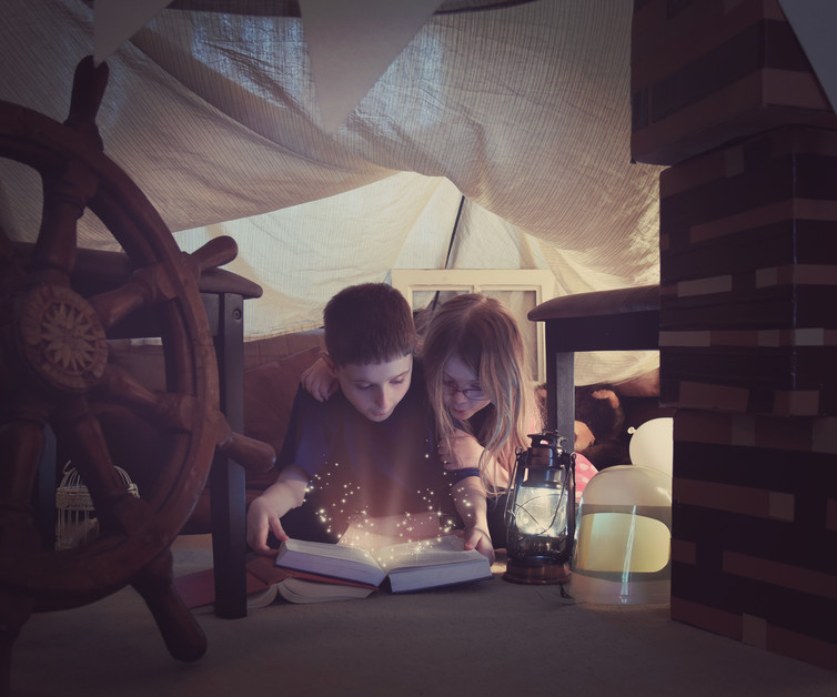 Two children reading under a homemade tent