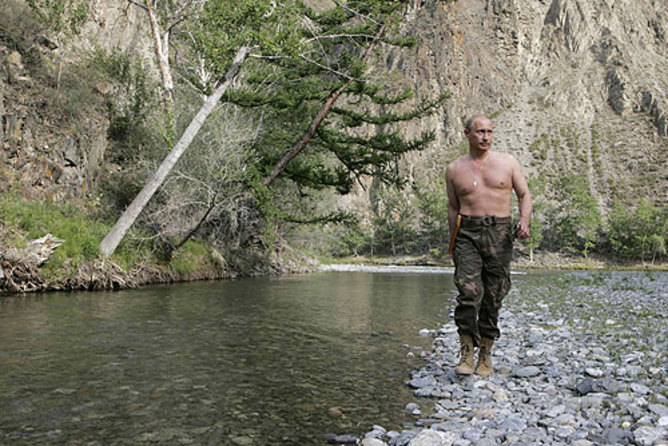 An image of Russian President Vladimir Putin walking along some natural stones without his top on and wearing khaki trousers. There is a stream alongside his right-hand side and trees on the bank lean in over it. Vladimir is looking to the left of the picture.