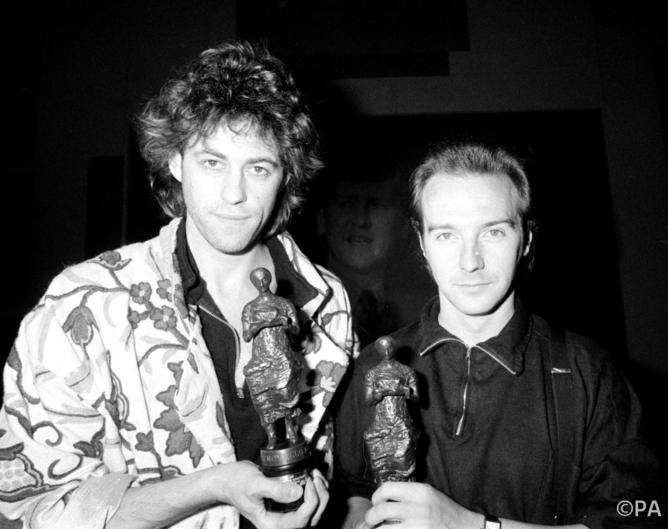 caption: Ure and Geldof with their 1984 Ivor Novello Awards for the Band Aid single.  PA/PA Archive