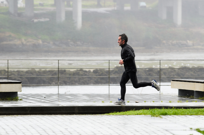 Man running along a pier beside Melbourne's Yarra River on a wet winter's day